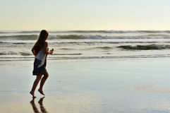 Young girl running  on the beach. Royalty Free Stock Image