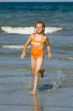 Young Girl Running on Beach. Young Girl in Braids Running through Surf on Beach Stock Photography