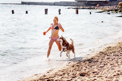 Young girl running on the beach with dog Royalty Free Stock Photography