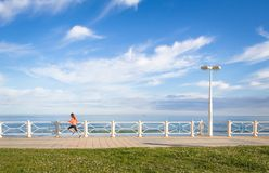 Young girl running in beach promenade on summer Royalty Free Stock Image