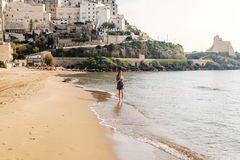 Young girl running on the beach of Sperlonga, Italy Stock Images