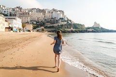 Young girl running on the beach of Sperlonga, Italy Stock Image