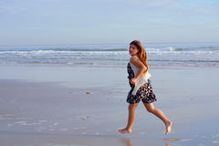 Young girl running on the beach. Stock Photo