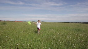 Young girl running with butterfly net stock footage