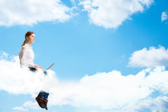 Young girl running in the clouds with a laptop Royalty Free Stock Images