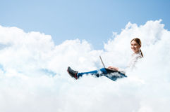 Young girl running in the clouds with a laptop Stock Photography