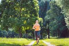 Young girl running down a path on meadow with weight dumbbells stock image