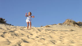 Young Girl Running Down Sand Dune Stock Image