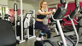 Young girl running on the exercise bike in the sport gym. Attractive girl running on the exercise bike in the sport gym.. Shot in 4K