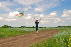 Girl flying a kite in a field stock image