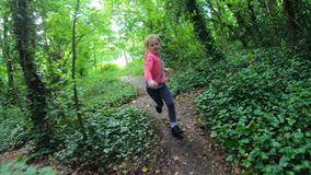 Young girl running in the forest. Cute Caucasian girl running fast through the narrow path in the forest stock video