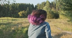 Young girl running her back with fluttering purple hair, background natural landscape golden hour.  stock footage