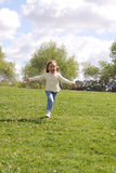 Young girl running on a lawn at park. Young girl running with open arms on a lawn at park stock images