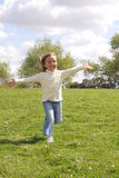 Young girl running with open arms. At park royalty free stock images