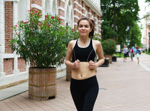 Young girl running in the park. It is engaged in fitness. Close-up. Healthy lifestyle image of young woman jogging outside Royalty Free Stock Photos