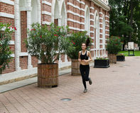 Young girl running in the park. It is engaged in fitness. Close-up. Healthy lifestyle image of young woman jogging outside Stock Photos