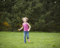 Young girl running through park in summer Stock Image