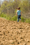 Young Girl Running on a Plowed Field Royalty Free Stock Images