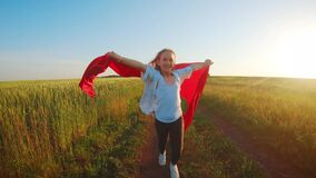 Young girl running with red tissue in green field. Happy cute girl playing in the wheat field on a warm summer day at