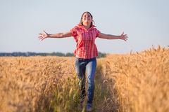 Young girl running on ripe wheat field. Happy young girl running on ripe wheat field at sunny day Stock Photo