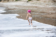 Young girl running by the sea surf foam Stock Images
