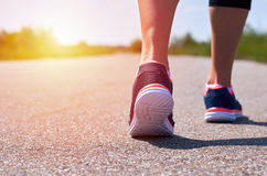 Young girl in running shoes runs along road, only her legs are visible, legs and sneakers, sunlight.  stock image