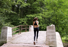 Young girl running in the summer forest. It is engaged in fitness. Close-up. Healthy lifestyle image of young woman jogging outside. View from a back Royalty Free Stock Photography
