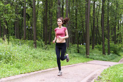 Young girl running in the summer forest. It is engaged in fitness. Close-up. Healthy lifestyle image of young woman jogging outside Royalty Free Stock Photos