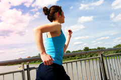 Young girl running in thr city, over the river by the bridge, Stock Photos
