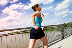 Young girl running in thr city, over the river by the bridge. Royalty Free Stock Photo