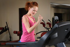 Young girl running at treadmill in gym Stock Images