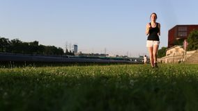 Young girl runs across the grass to the camera. stock footage