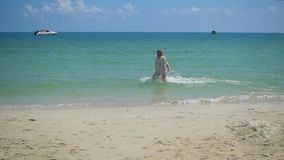 A young girl runs along the beach, creating a spray of water. Tropical island, on a hot day stock footage