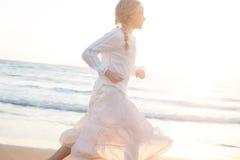 Young Girl Runs along the Sandy Beach of the Sea Royalty Free Stock Photos