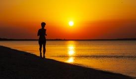 Young girl runs along the sea coast Stock Image