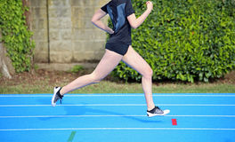 Young girl runs on the athletics track during sports training. Young girl runs fast on the athletics track during sports training Stock Images
