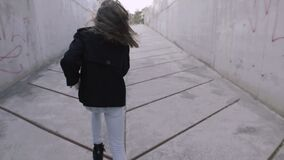 A young girl runs through a dark concrete tunnel to the glowing end. Beautiful teenage girl runs out into the light and rejoices stock video footage