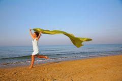 Young girl runs on edge of sea with yellow shawl royalty free stock photos
