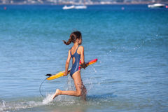 Young girl runs with her surfboard in the water Stock Image