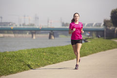 Young girl runs on Jogging track along the river in a big city. Royalty Free Stock Images