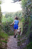 Young girl runs with a puppy along a coastal path Royalty Free Stock Photo