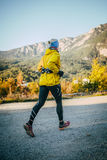 Young girl runs on road on background of mountain landscape Stock Photography