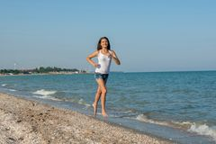 Young girl runs on the sea Royalty Free Stock Photography