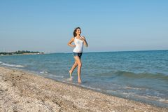 Young girl runs on the sea Stock Photography