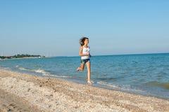 Young girl runs on the sea Stock Photos