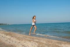 Young girl runs on the sea Stock Photo