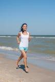 Young girl runs on the sea Stock Image