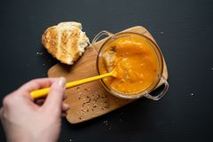 Pumpkin soup, a wooden board on a black background, a piece of bread, sesame and flax seeds stock images