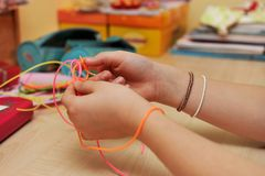 Young girl`s hands weaving a plastic bracelet close-up. Young girl`s hands weaving a diy colorful plastic bracelet close-up Stock Photos