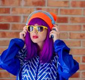 Young girl in 90s sports jacket and hat. On brick wall background royalty free stock photography